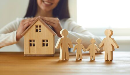 Family home insurance mortgage rental construction loan concept. Womans hands with a model of the house and figures of seven people on the table against the background of the window. Banque d'images - 137129653