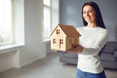 Happy couple holding a mock up of a house in their hands while standing in a room at home. The concept of housewarming, a new house, apartment, room, moving. Banque d'images - 137129654
