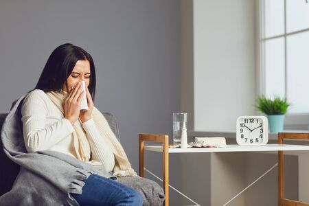 Sick girl sneezing nose sitting on a sofa under a blanket with the symptoms of the flu disease virus has pills in the room. Banque d'images - 137129656