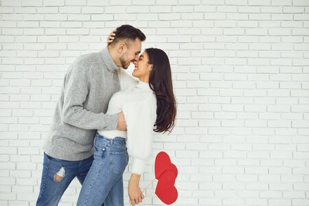 Concert Valentines Day. Young couple kissing with hearts in hands on a white brick background. Banque d'images - 137129667