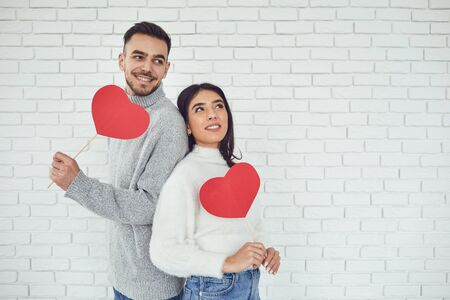 Concert Valentines Day. Young couple with hearts in hands on a white brick background. Banque d'images - 137129668