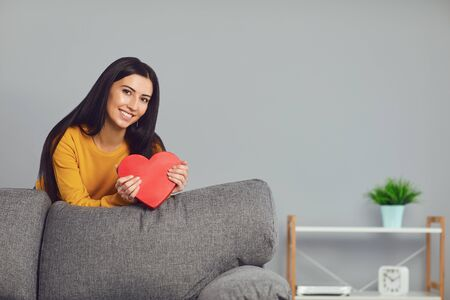 Beautiful girl holding a red heart in her hands while sitting on a sofa in a gray room. Valentines day. Banque d'images - 137129670
