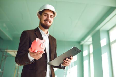 The concept of savings in construction. The builder foreman is holding a piggy bank in his hand. Banque d'images - 137129672