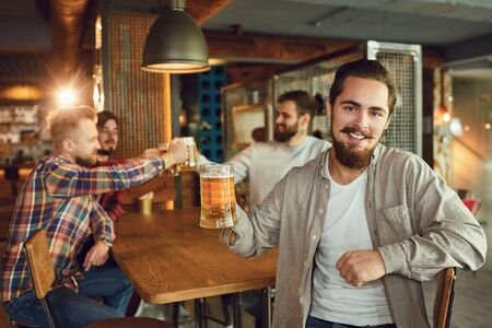 Group of male friends drink beer at a party in a bar. Friends meeting. Young people drink alcohol in a restaurant. Banque d'images - 137129675