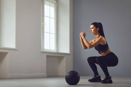 Squat exercises. Athletic brunette girl in black sportswear with dumbbells in her hands doing squats in a room indoors. Banque d'images - 137184411