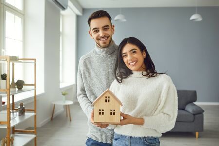 Happy couple holding a mock up of a house in their hands while standing in a room at home. The concept of housewarming, a new house, apartment, room, moving. Banque d'images - 137184702