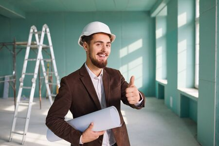 Foreman bearded man in a white helmet in a room at a construction site. Banque d'images - 137188533