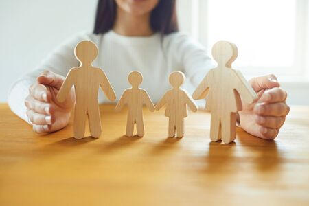 In the hands of a woman is a family of wooden figures. Family Planning Protection Concept. Banque d'images - 137165586
