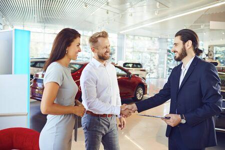 A couple buys a new car. A man and a car salesman make a handshake at a car dealership. Buying rental a car.