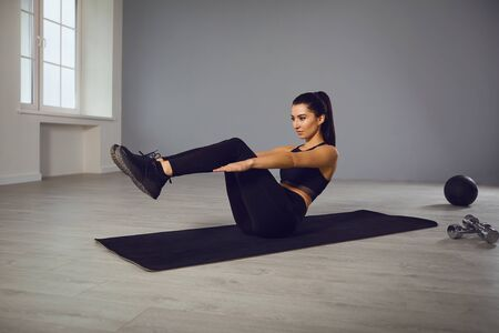 Exercises abs. Athletic brunette girl in black sportswear doing abc exercises in room indoors.