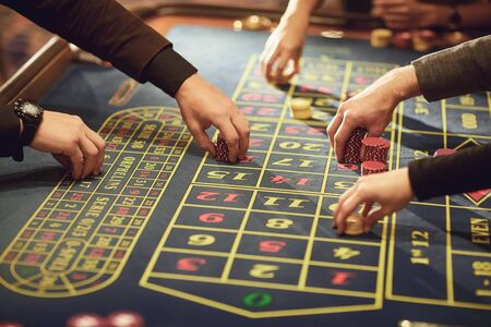 A hand with chips makes a bet on roulette in a casino. Gambling Betting.