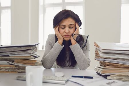 Frau brünette Geschäftsfrau in Gläsern mit einem Berg von Dokumenten auf dem Tisch müde depressiv abgemagert enttäuscht enttäuscht depressiv am Tisch im Büro.