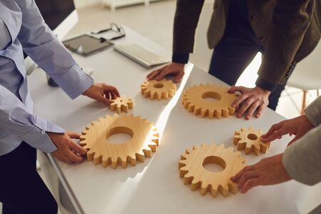 Business people holding wooden gears in their hands connect at a business meeting in the office. Concept of partnership creative work startup startup teamwork team business people.