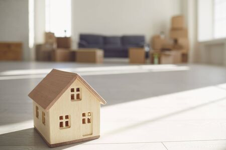 Concept of a new home apartment housing real estate purchase lease sale investment mortgage. Model of a wooden house on the floor in a new bright sunny house.