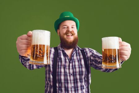 Happy St. Patricks Day.Fat man in a green hat holds his hands up glasses with beer on a green background. Foto de archivo