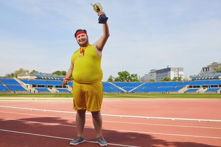 A fat man in sportswear rejoices in victory, holds a cup in his hands. Winner motivation concept.