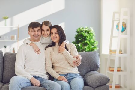 Happy family at home. Mother father and daughter sitting on sofa smiling cheerfully in room interior.