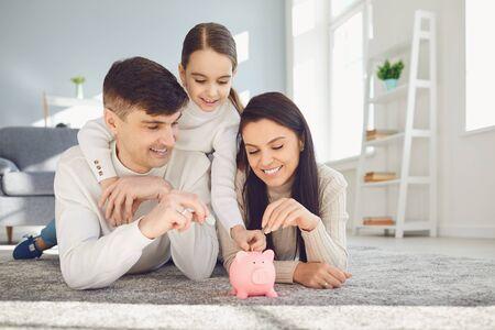 Familia feliz ahorra dinero en una alcancía de cerdo. Concepto de ahorro de finanzas de dinero. Foto de archivo