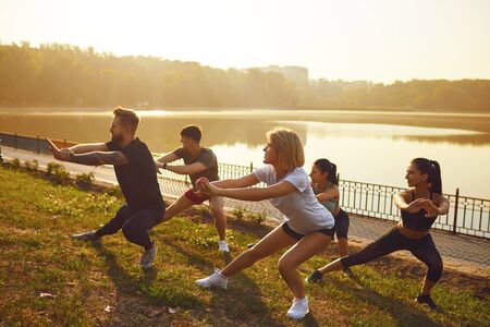 Group of young active people at a training session in a park by the lake.