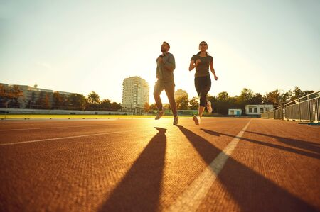 Young man and woman runners run in the morning at dawn.Jogging. Health. Healthy lifestyle. Zdjęcie Seryjne