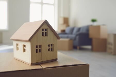 Concept of a new home apartment housing real estate purchase lease sale investment mortgage. Model of a wooden house on the floor in a new bright sunny house. Imagens
