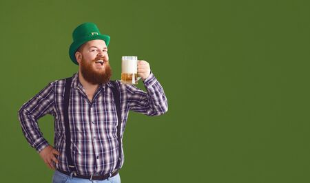 Happy St. Patricks Day.Fat man in a green hat holds his hands up glasses with beer on a green background.