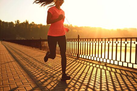 Runner runs on the road in the sun at sunset in an autumn park. Jogging for health.