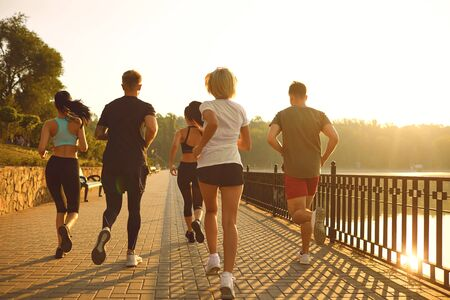 A group of young people in sportswear are running in the park. Back view. Standard-Bild
