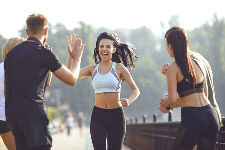 Une coureuse s'amuse avec un groupe d'amis dans un parc le matin en été en automne. Mode de vie actif. Le jogging. Santé. Mode de vie sain.