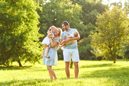 Family with baby stands on green grass in the park with sunlight in summer. The concept of a happy family.