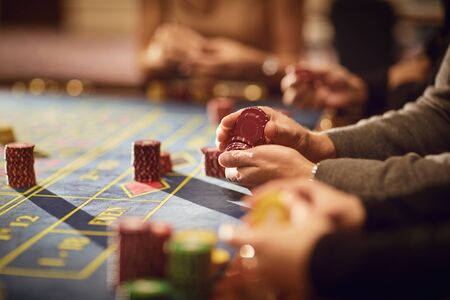 People gamblers play make bets while sitting at the roulette table in a casino. Imagens