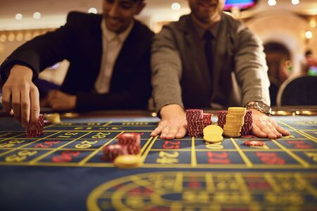 Close up of people hands laying chips on roulette table in casino. A group of people bet on gambling.People gamble at the roulette table.