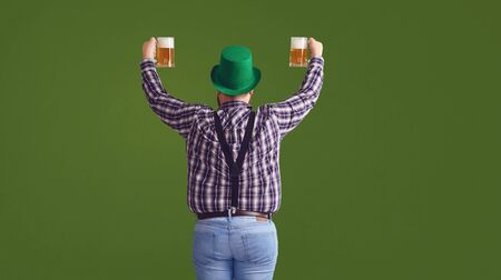 Happy St. Patricks Day. Back view a fat man in a green hat holds his hands up glasses with beer on a green background. Foto de archivo