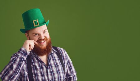 Happy St. Patricks Day. Fat funny bearded red-haired man in a green hat smiles on a green background Patricks Day.