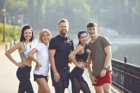 A group of athletes training in the park. Friends in sportswear portrait standing outdoors in the morning. Healthy lifestyle.