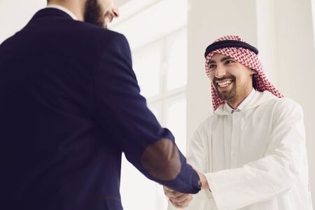 Handshake of arabic and european businesspeople. Businesspeople hands makes a handshake in the office. The conclusion of the contract by business people.