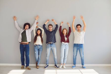 Group of young people students in casual clothes cheerfully raise their hands up while standing against a gray background. Friends together on a gray wall. Friendship students. Standard-Bild