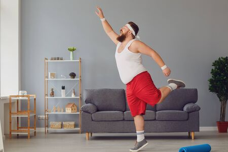 Funny red fat man doing exercises while standing at home. The concept of losing weight sports exercise healthy lifestyle.