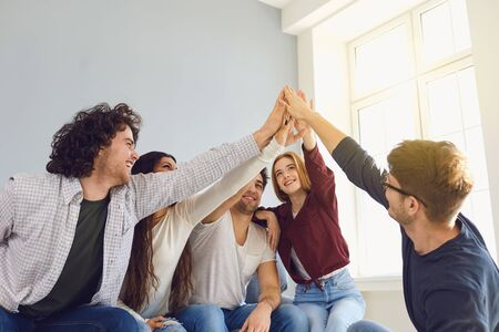 Happy friends cheerfully raised their hands up in a room with a window. Friendship Team Connection Communication Friendship Concept.