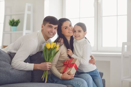 Happy mothers day. Father and baby daughter congratulates mom with flowers and a postcard in a room with a window.