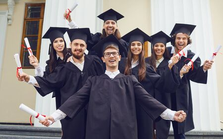 A group of graduates with scrolls in their hands are smiling against the background of the university. Graduation.University gesture and people concept.