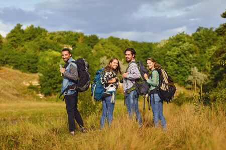 A group of tourists with backpacks is walking in nature.