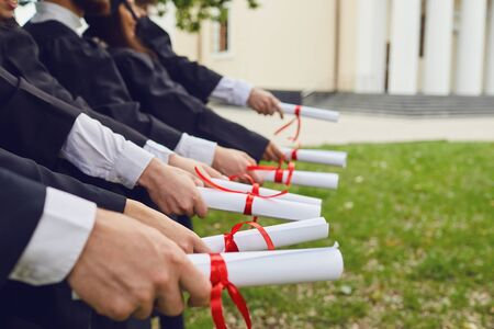 Scrolls of diplomas in the hands of a group of graduates. Graduation.University gesture and people concept.