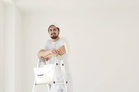A male painter in a white uniform with a roller works in his hand in a white room.