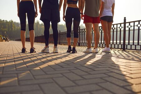 A group of young people runs along the road in the park in the morning at dawn. Jogging for health.The legs of the athletes run in the park in the morning.