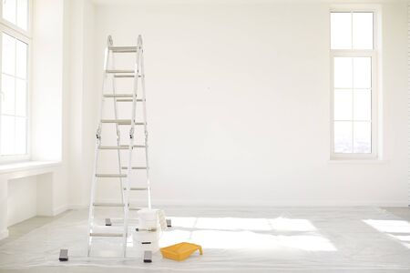 Painting in a white room with windows with a stepladder and paints on the floor. Standard-Bild