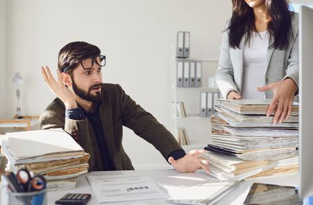 Worker businessman tired upset indignant unhappy sitting at workplace looks at a large amount of work in the office.