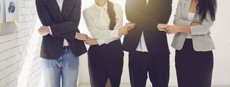 Creative faceless business people team holding hands while standing indoors. Concept business team creativity meeting analytics decision.