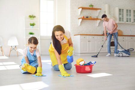 Une famille heureuse nettoie la pièce de la maison. La mère et la petite fille se lavent dans des gants tout en étant assises par terre en souriant joyeusement. Lavage hygiénique. Banque d'images