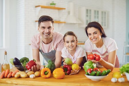Beautiful happy family smiling at a table with fresh vegetables make salad in the kitchen. Mother father and little daughter make healthy food fresh vegetables in room.